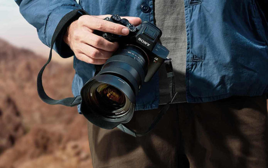 Sony Alpha A7IV with lens being held by a person